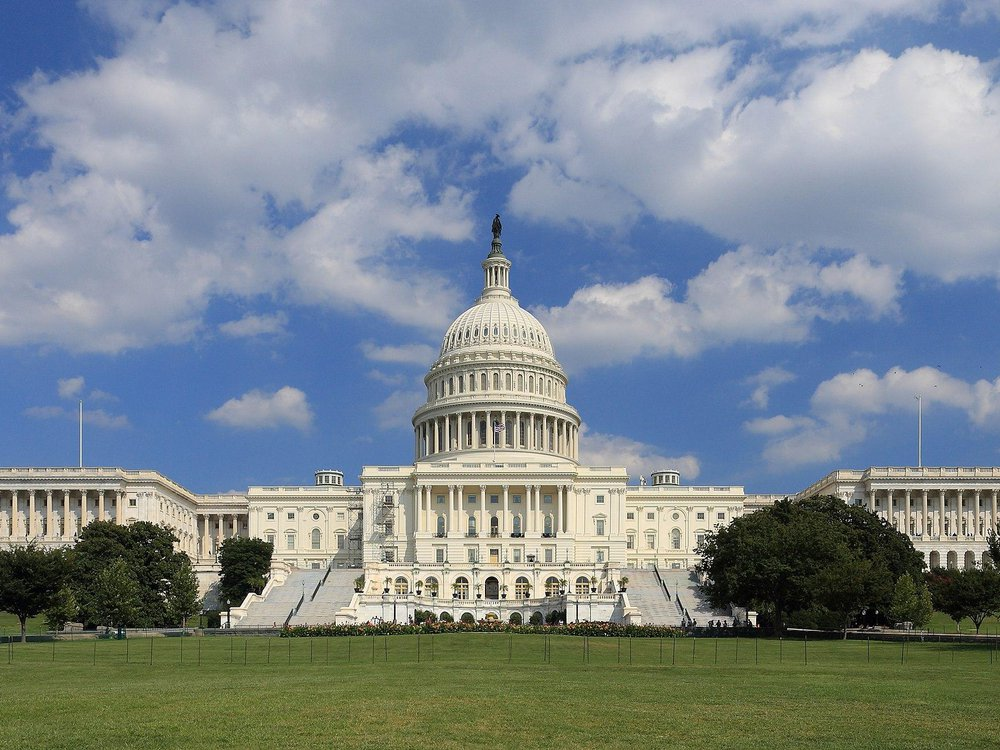 The US Capitol building, pictured on a bright sunny day with blue sky and white fluffy clouds behind