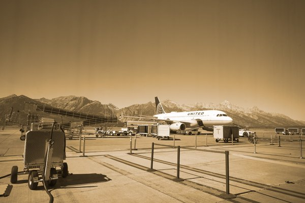 An airplane at Jackson Hole Airport.  Grand Teton mountains in the background. thumbnail