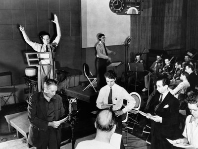 Orson Welles (arms raised) rehearses his radio depiction of H.G. Wells' classic, The War of the Worlds. The broadcast, which aired on October 30, 1938, and claimed that aliens from Mars had invaded New Jersey, terrified thousands of Americans.
