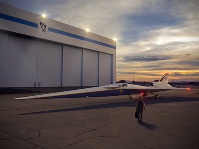 An artist's concept of the low-boom flight demonstrator outside the Lockheed Martin Aeronautics Company's Skunk Works hangar in Palmdale, California.