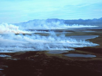 A lightning-caused wildfire in 2013 creates white smoke rising from the tundra in front of the Baird Mountains.