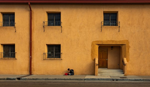A girl texting near a yellow building thumbnail