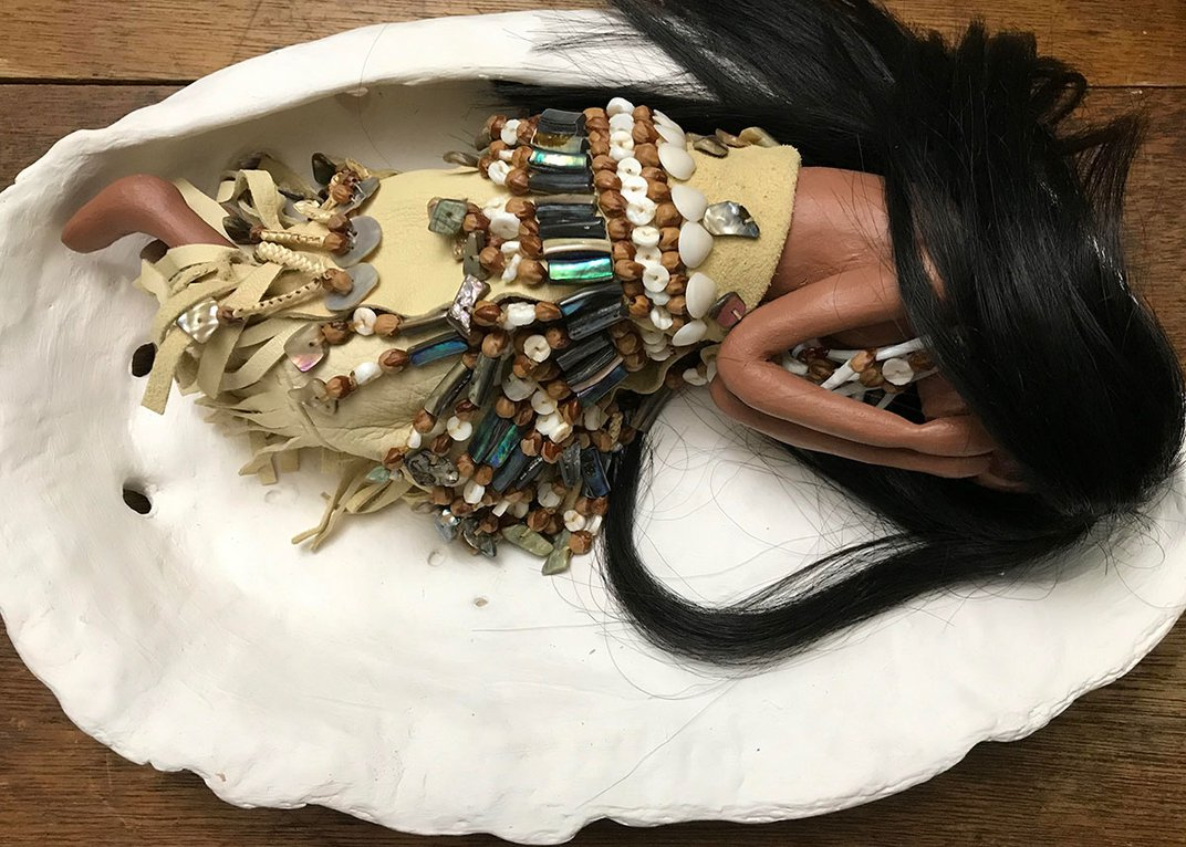 Sculptural art piece of a figure of a woman curled up in fetal position inside an actual abalone shell. She is holding her hands to her face, as if crying, and wearing an intricately beaded dress.