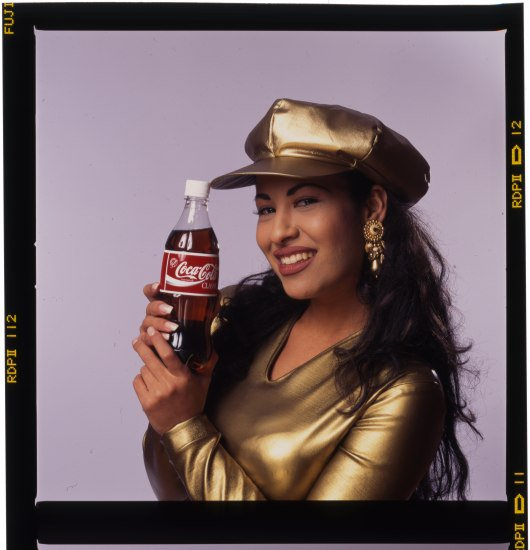 Selena in a gold cap holding a Coca-Cola bottle