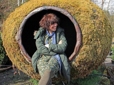 Mary Reynolds sits in a moss-covered pod designed by the West Cork artist Peter Little.