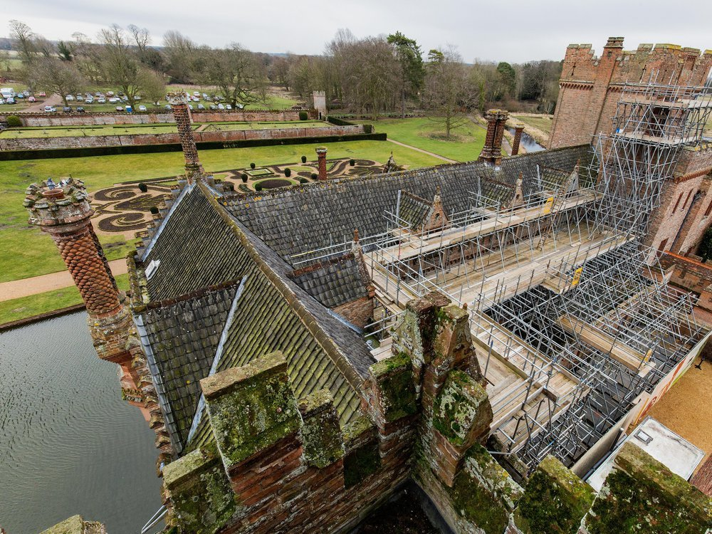 A view looking down on the roof of the Manor, with about half of its roof covered by scaffolding. Behind the house, which is covered in moss, there's a bit of moat and an ornate garden