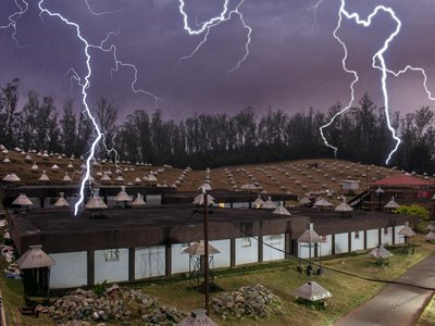 Illustration of the GRAPES-3 Muon telescope in a lightning storm.