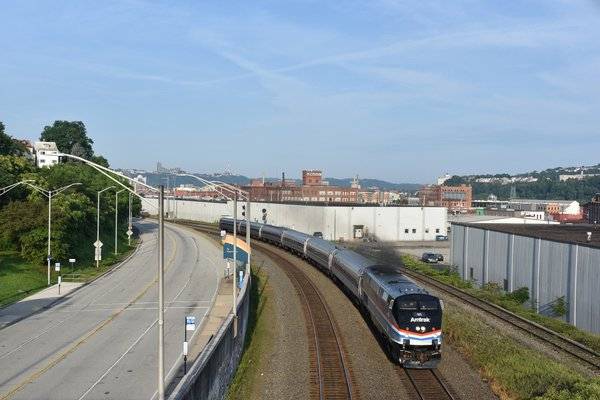 An Amtrak Train with old fashioned Pittsburgh buildings in background thumbnail