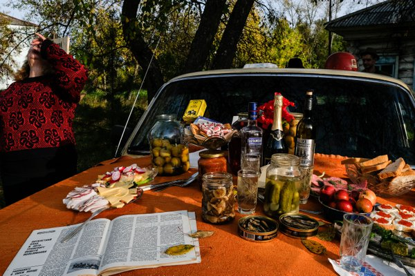 The typical Russian meal is on the hood of famous Soviet car called Volga for visitors of the motorcycle's contest in Irbit, Ural, Russia