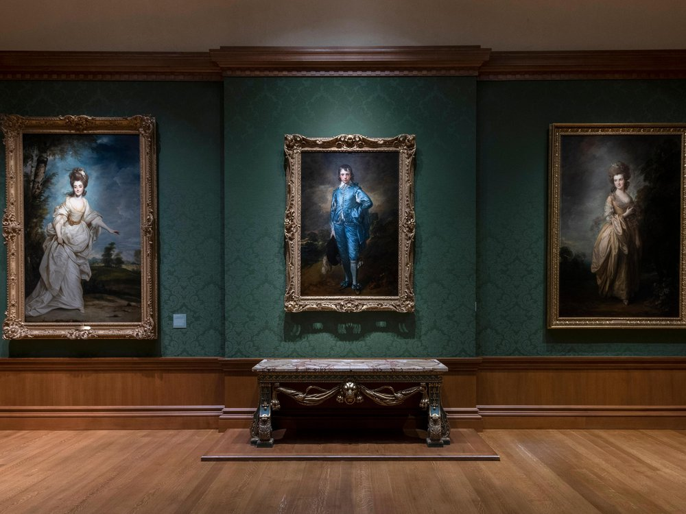 A dark green room with The Blue Boy hanging in the center of the frame and two other portraits on either side of him