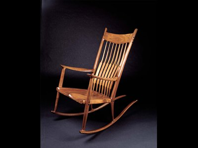 """The sensuous curves and subtle walnut grain of Maloof's rocker just seem to beckon and say """"Come on in a sit a while."""""""