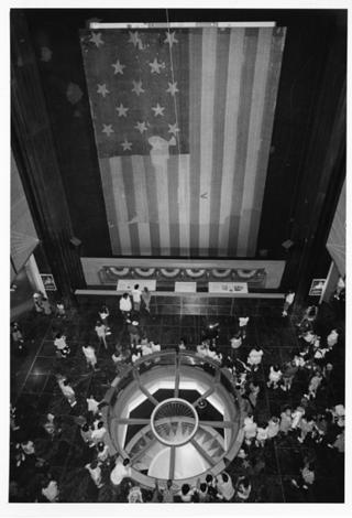 Black and white photo of flag hanging in rotunda