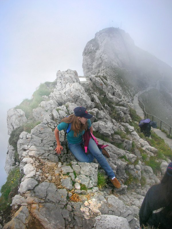 A girl sitting among clouds on a ridge of Mount Pilatus near Lucerne, Switzerland thumbnail