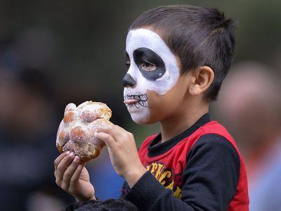 A zombie enjoys a bite of pan de muertos at a Day of the Dead celebration in Atlanta, Georgia.