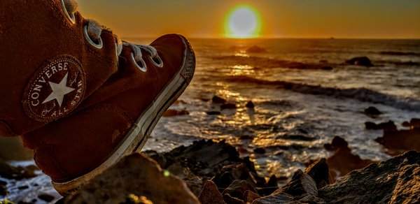 Converse over ocean cliff-side sunset thumbnail