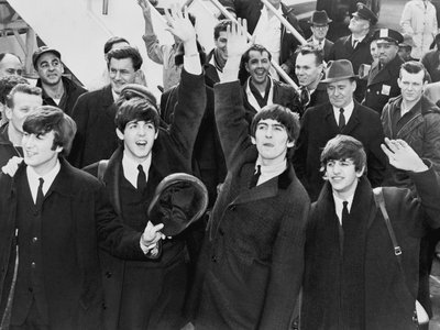 The Beatles step onto the tarmac at JFK Airport on February 7, 1964, arriving for their first performance in the U.S.