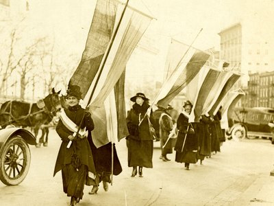 In 1917 when it was highly unusual for women to protest, a suffrage procession walked the streets of Washington, D.C. towards the White House carrying purple, white and gold banners.