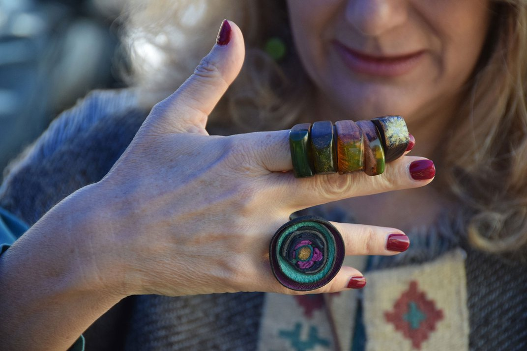 A woman holds her hand in front of her face.  On her fingers are several brightly colored glass rings.