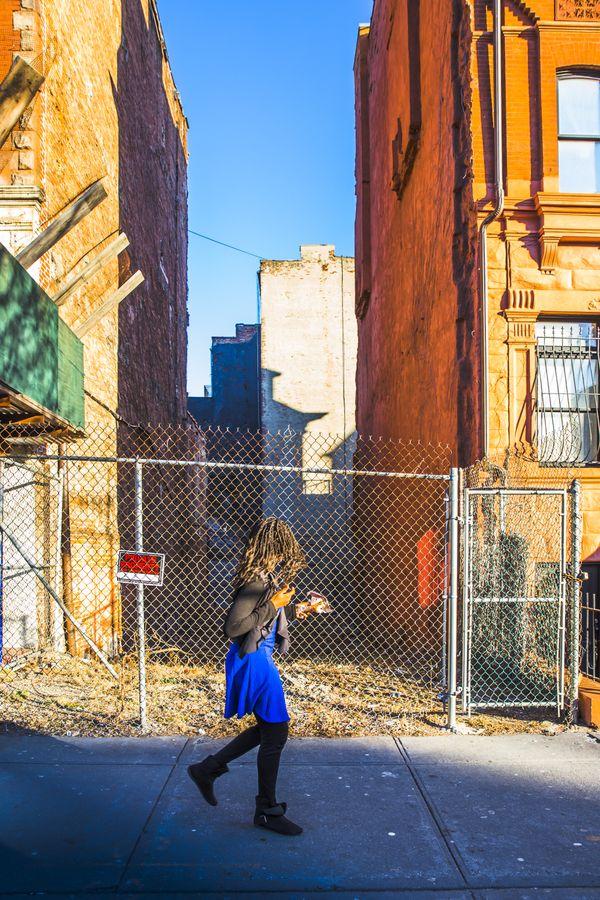 Girl walking past vacant lot thumbnail