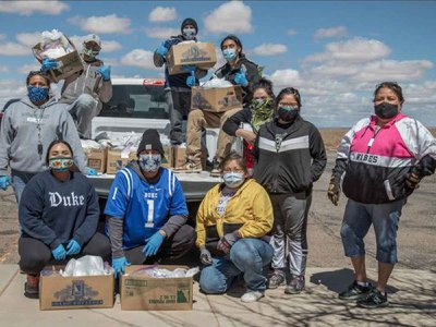 Volunteers with the Navajo & Hopi Families Covid-19 Relief Fund distribute food and other essential supplies to isolated communities and farmsteads on Navajo Nation and Hopi lands. As part of the Smithsonian's virtual program 24 Hours in a Time of Change, Shandiin Herrera (Diné)—seated on the left, wearing a Duke University sweatshirt—describes how this grassroots response to the COVID-19 pandemic came together last March and shares her experiences as the fund's volunteer coordinator in Monument Valley, Utah.