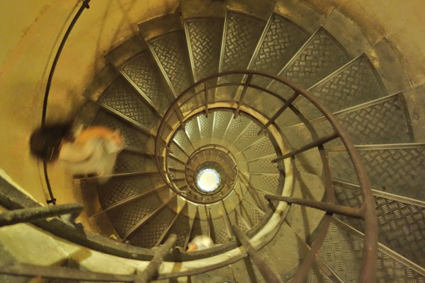 Lady racing down the spiral stairs of Arc De Triomphe, Paris thumbnail