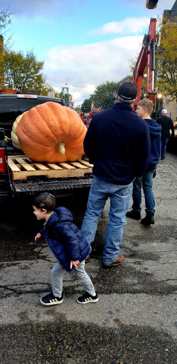 Young Boone Ritchie running by his papaw Tim Ritchie's giant pumpkin at the Circleville, Ohio Pumpkin Show. 10-15-2019 thumbnail