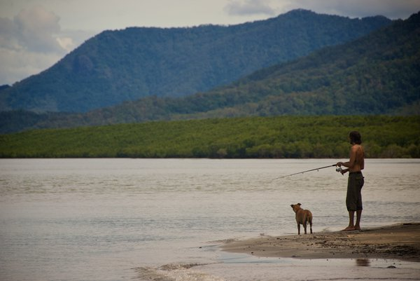Man and his dog fishing off Four Mile Beach, Port Douglas, Queensland thumbnail