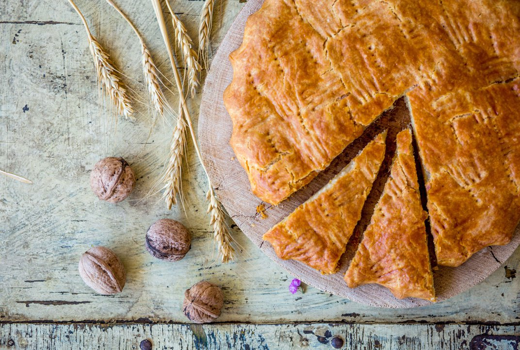 Delicately arranged on a wooden plate is an a warm, orange-toned loaf of bread. Aside it are placed a few walnuts and pieces of wheat.