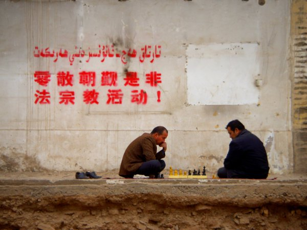 """Uighur men contemplate their next move under a sign that reads """"Practicing Religion is Prohibited."""" thumbnail"""