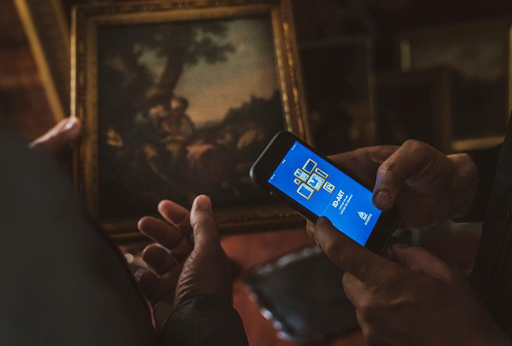 A dark image of two people's hands; one person holds a work of art in a gilt frame, while the other holds a phone with the Interpol app opened