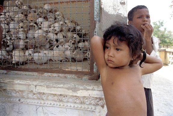 Children stand near a memorial at Cambodia's killing fields