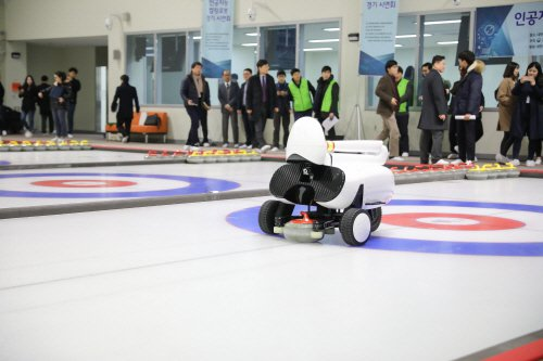 """A white robot with a teardrop-shaped """"head"""" appears to crouch down, rolling on wheels, as it pushes a round curling stone forward over ice; many onlookers watching"""
