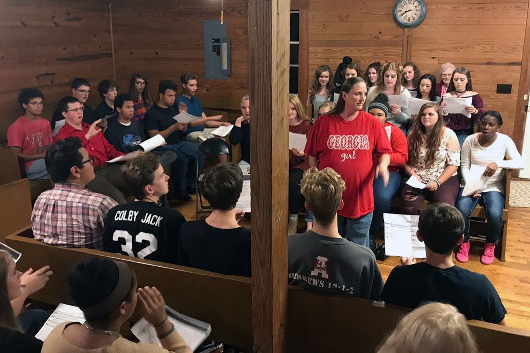 """Students sit in pews on three sides of a woman in a red """"Georgia Girl"""" shirt in the center."""