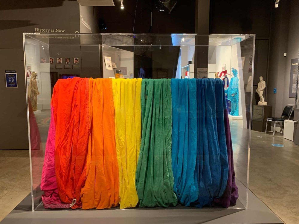 A view of a museum display case with the gathered folds of a piece of rainbow-striped cloth, including 8 bright colors from pink to purple