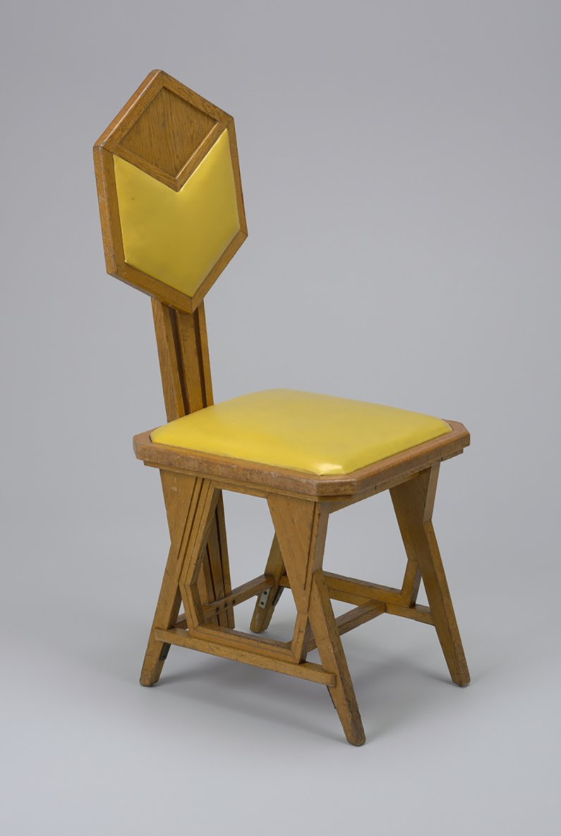 A oak side chair with yellow leatherette cushions on the square seat and back
