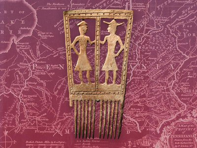 In this late 17th-century comb, created by a craftsperson from either the Seneca or Susquehannock peoples, two animated figures wearing frock coats—likely a Native American and a Euro-American—face one another.