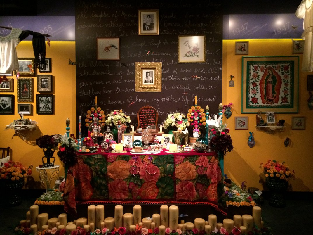Elaborate and colorful altar built on a bedpost, with photos, food, dozens of candles, marigolds and roses, and other handmade details