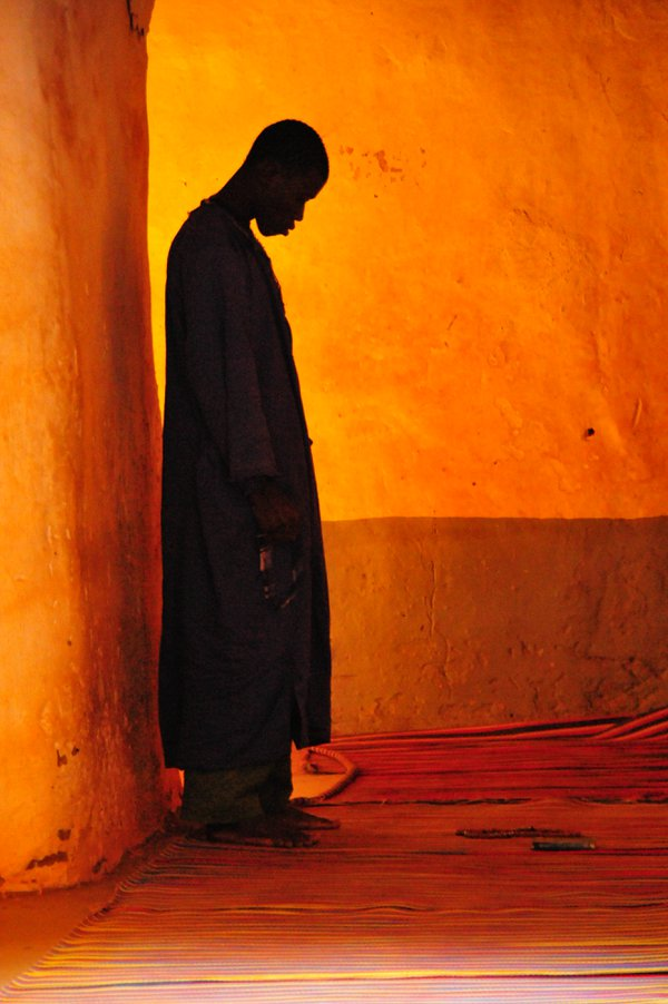 In a dusty mosque in Mali a man prays.   trying not to disturb the man I waited quietly and took this photo. thumbnail