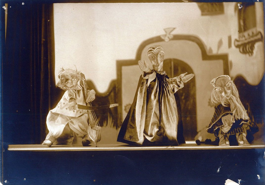 Three handmade puppets stand in front of a set of a palace. The puppet on the far left holds a prop cello, the puppet in the middle stands with his hands open, and the puppet to the far right is crouched down.