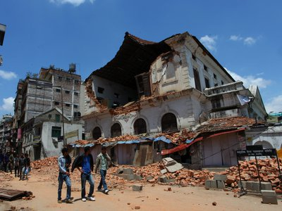 People walk past the damaged Durbar High School a few days after the major earthquake that struck Nepal in April.