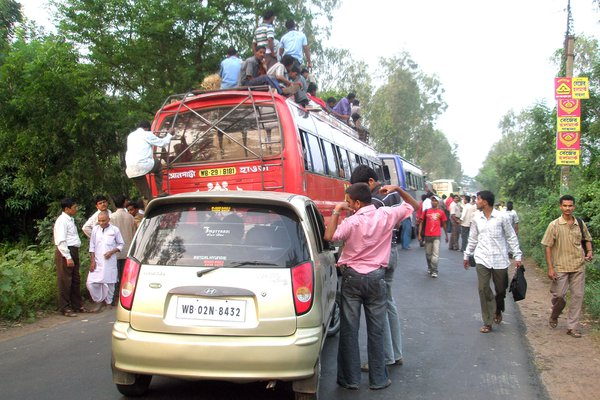 People are travelling roof on the bus due to no room inside the bus and waiting for trafic jam on the high way. thumbnail