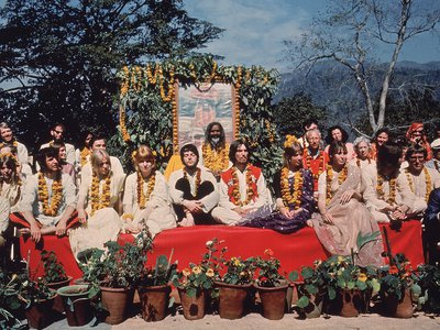 John Lennon chats with Mike Love (far right, in dark blue) as the Beatles sit for a photo with Maharishi and other course participants.