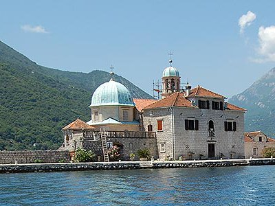 """On the Bay of Kotor, young men motor travelers out to """"Our Lady of the Rocks"""" Church."""