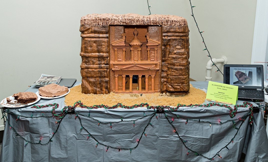 Orange cake recreation of Petra on a rectangular table with a blue-gray tablecloth.