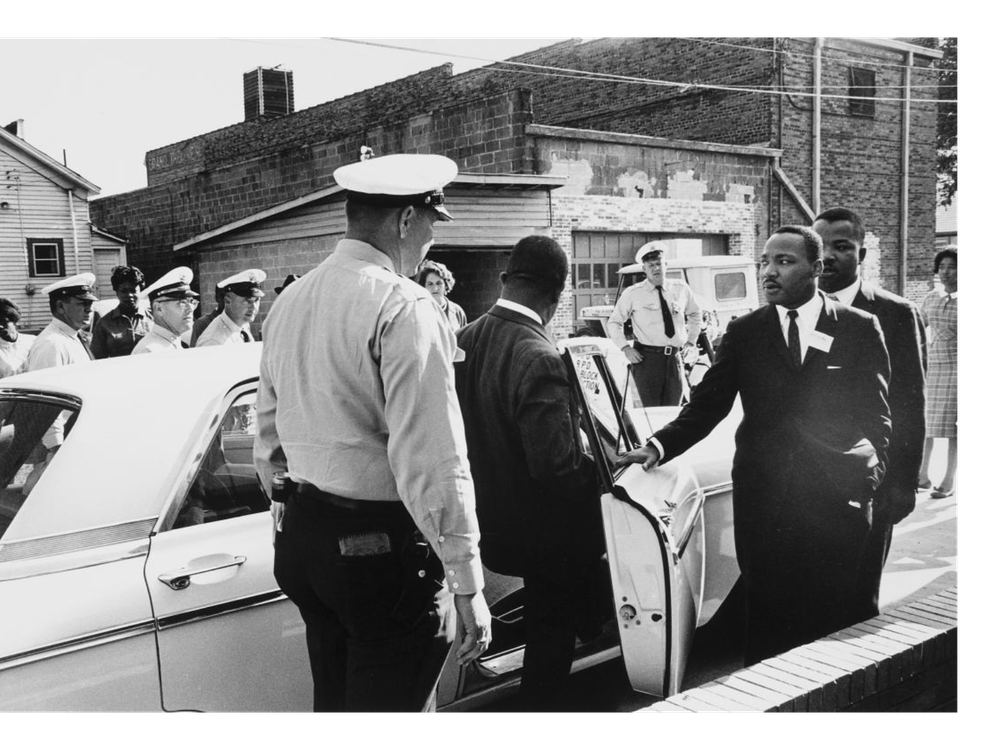 A black and white photograph of policeman in foreground, one man stepping into a squad car and MLK with an arm outstretched moving toward the car