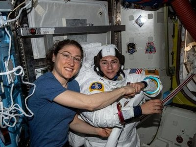 Christina Koch (left) poses for a portrait with Jessica Meir while preparing for their first spacewalk together.