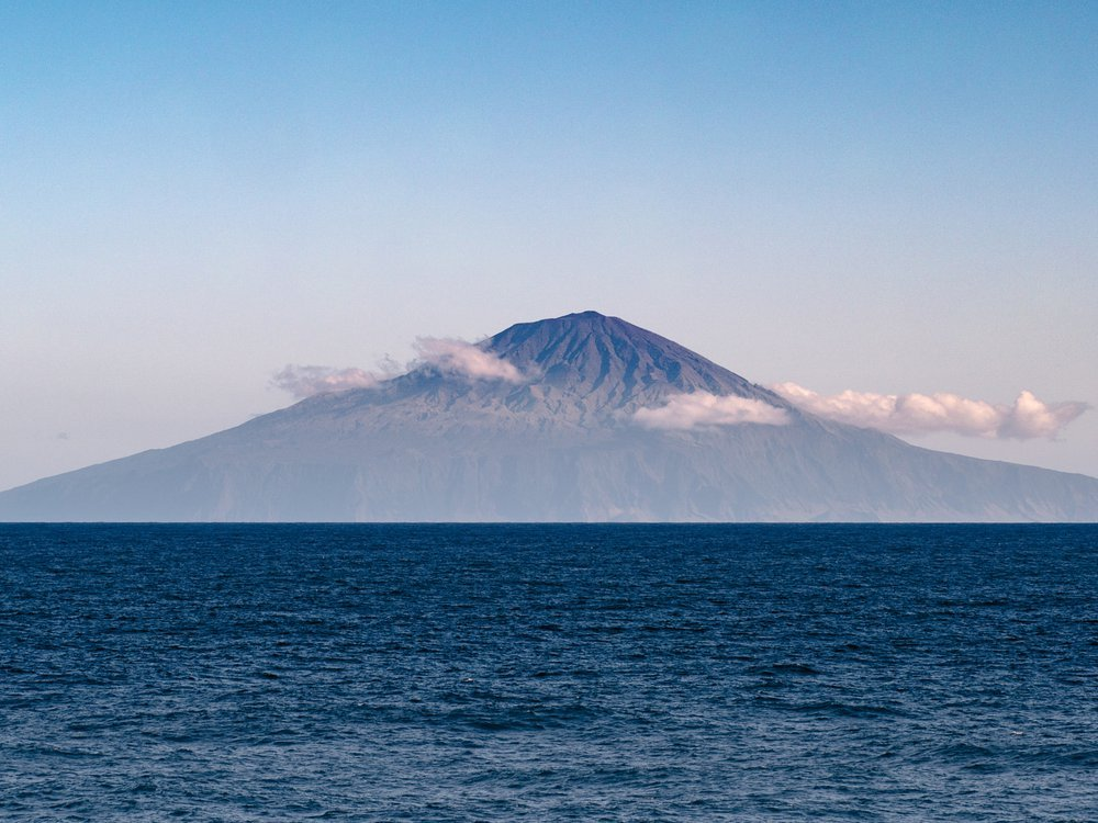 A photograph of Tristan da Cunha taken from a boat out at sea. The blue ocean water meets the horizon halfway up the photo. The island, shaped like a flat triangle sits at the horizon. It has small clouds in front of it and a blue-pink sky in the backgrou