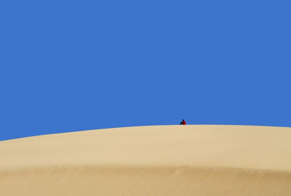 Boy in a football strip resting on a sand dune thumbnail