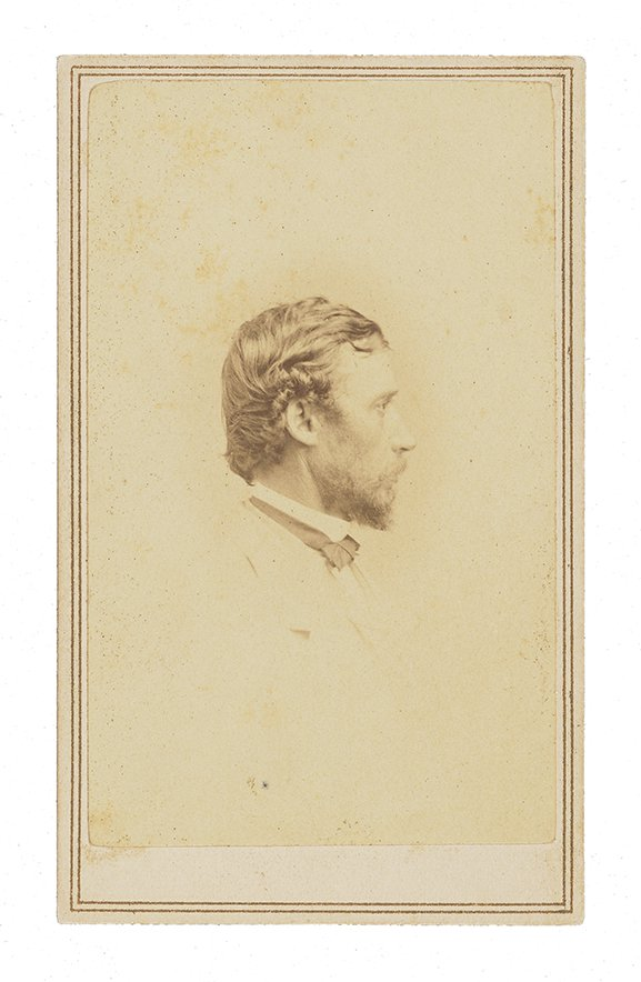 Formal studio photograph portrait of Sanford Robinson Gifford. He is in profile facing right, wearing a white suit and black bow tie. Image is cropped from his elbow up.