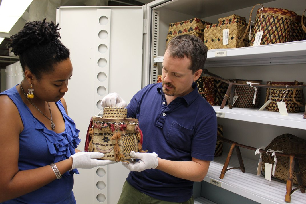Two people standing in front of a cabinet of museum objects.
